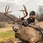 Hunter with harvested buck.
